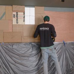 """An artist works on the restaurant's """"package wall."""""""