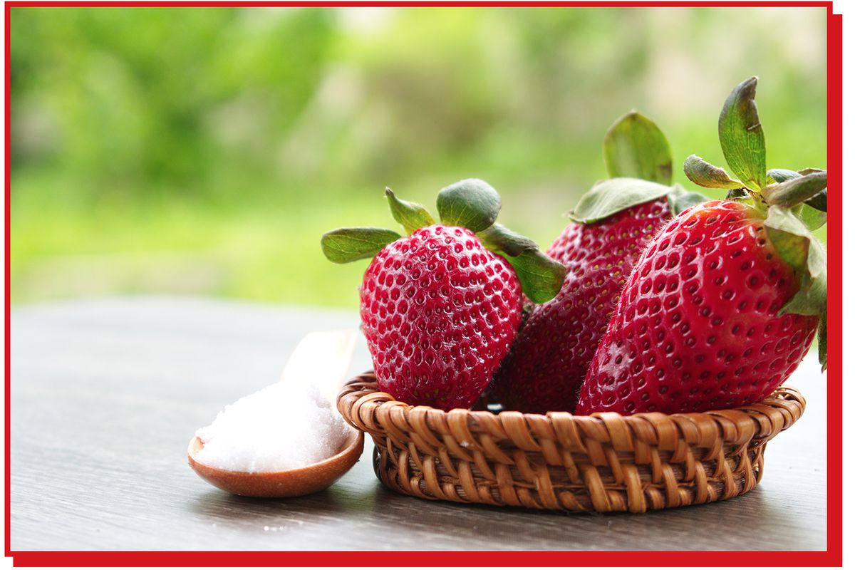 Four strawberries in a small bowl next to a spoon of salt.