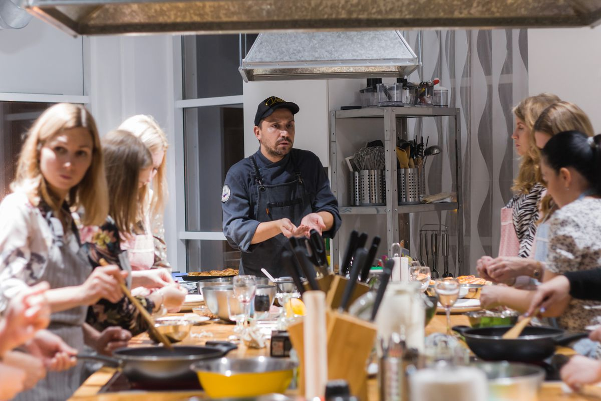 A man stands in front of a group at a cooking class.