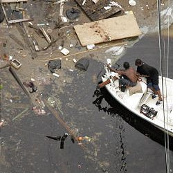 Two men ride in a boat search Thursday through floodwaters left by Hurricane Katrina in New Orleans.