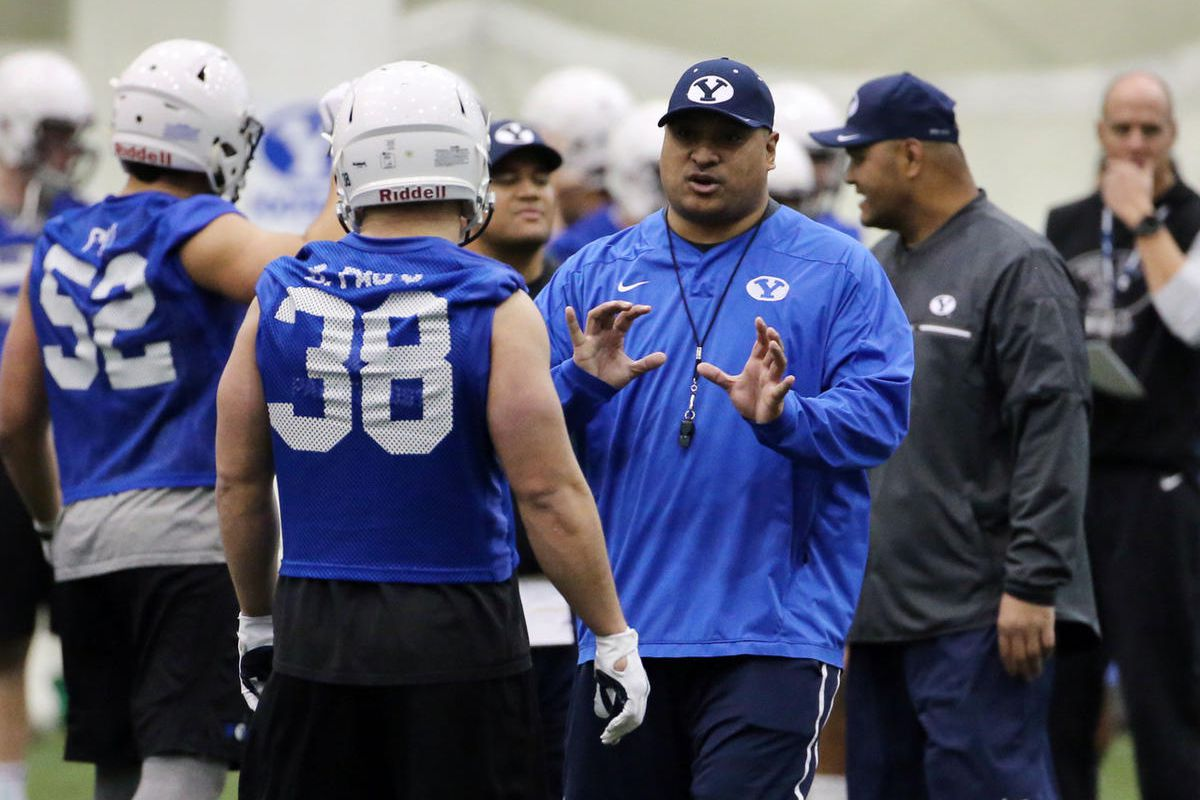 Head coach Kalani Sitake gives instructions to Butch Pau'u during Brigham Young University football practice in Provo on Monday, Feb. 27, 2017.