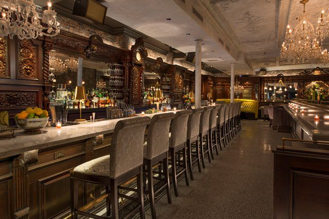 Interior shot of a swanky bar with dark wood, a muted color palette, and crystal chandeliers