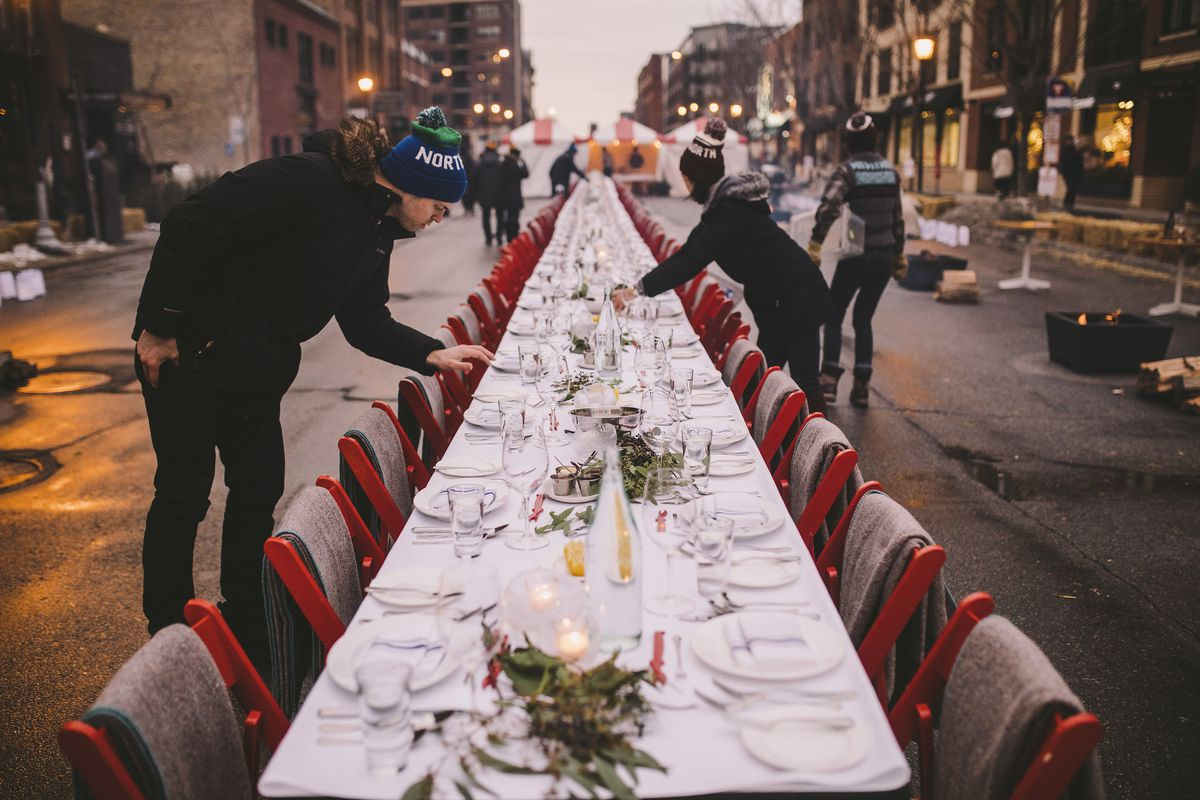 """A winter table set outside, a server in a """"North"""" hat sets the table"""