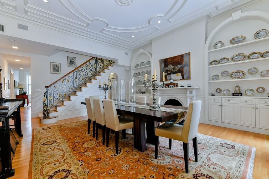 A dining room with a table and chairs as well as built-in shelves and a staircase leading into the room.