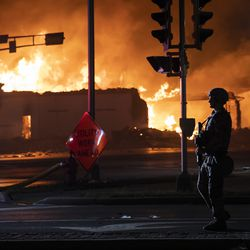 A member of the Wisconsin National Guard stands watch outside one of several businesses burning during the second night of unrest after police shot Jacob Blake, Monday night, Aug. 24, 2020.