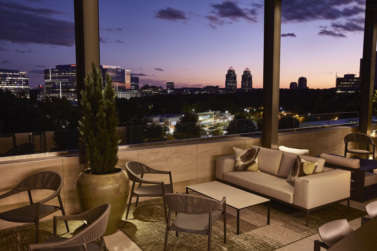 The covered outdoor seating area and lounge includes a bar and views of views of Perimeter Center and the King and Queen towers.