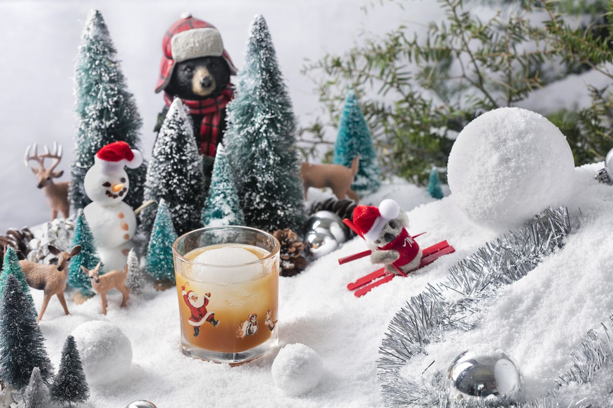 One of Miracle's holiday cocktails, photographed in a bucolic winter holiday backdrop that includes a snowman and a koala on skis
