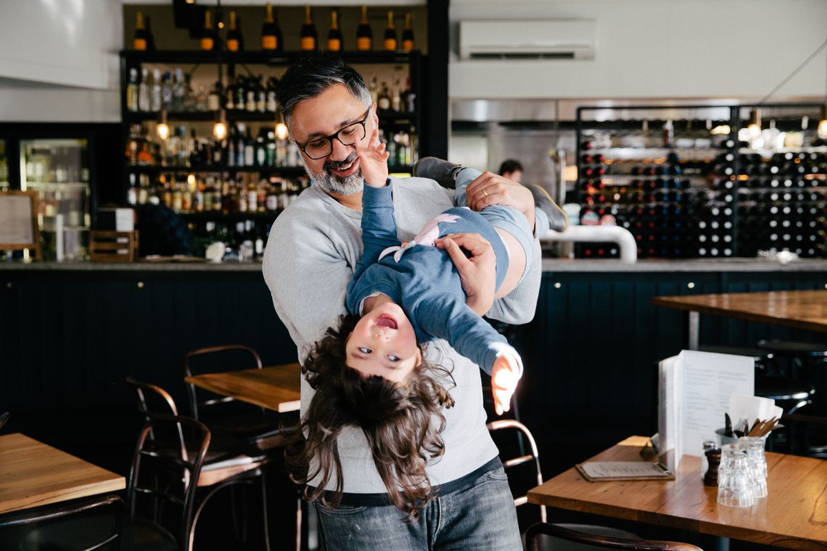 Dad Mark holds his giggling daughter upside down in a pub in Northcote