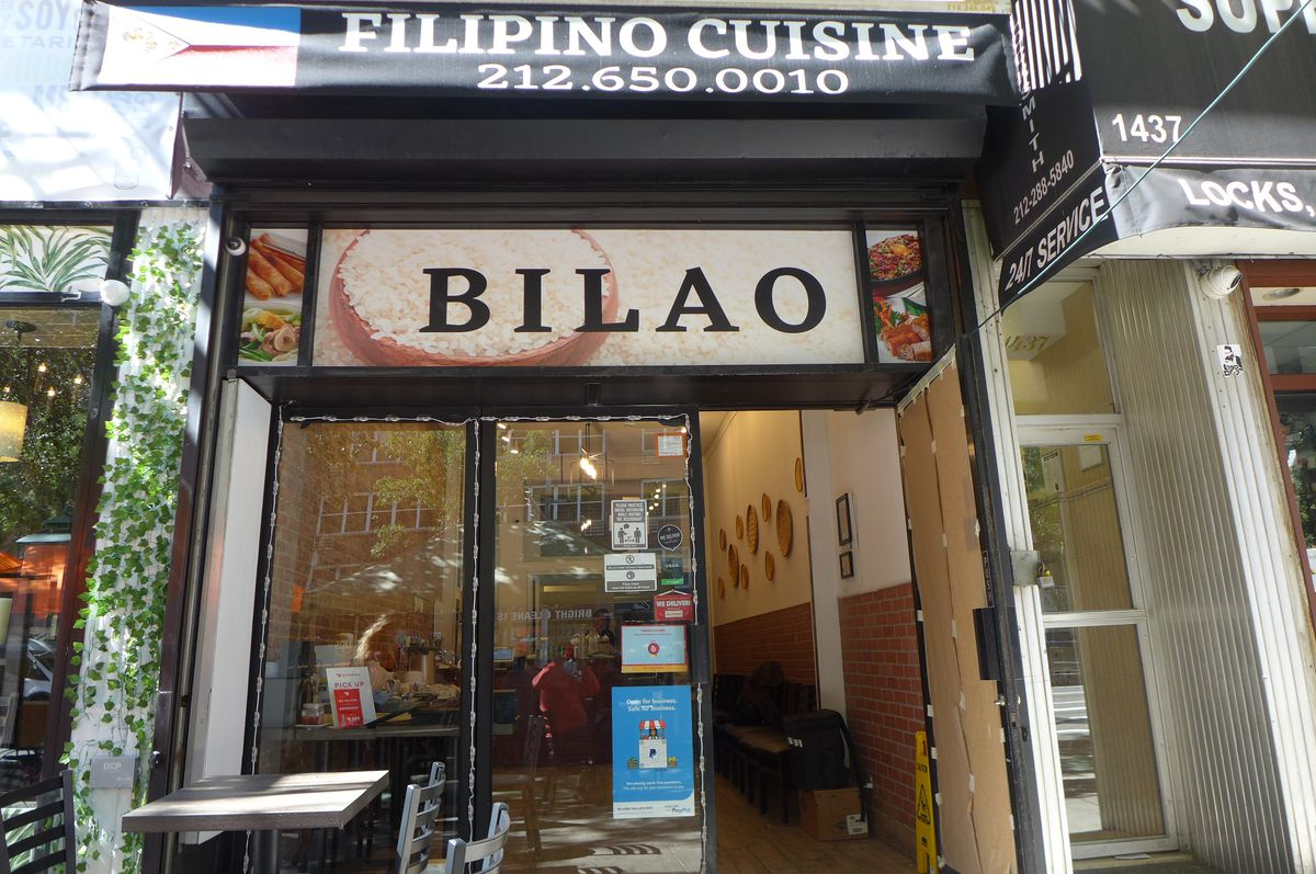 A plainish storefront that says Filipino Cuisine, with a table out front.
