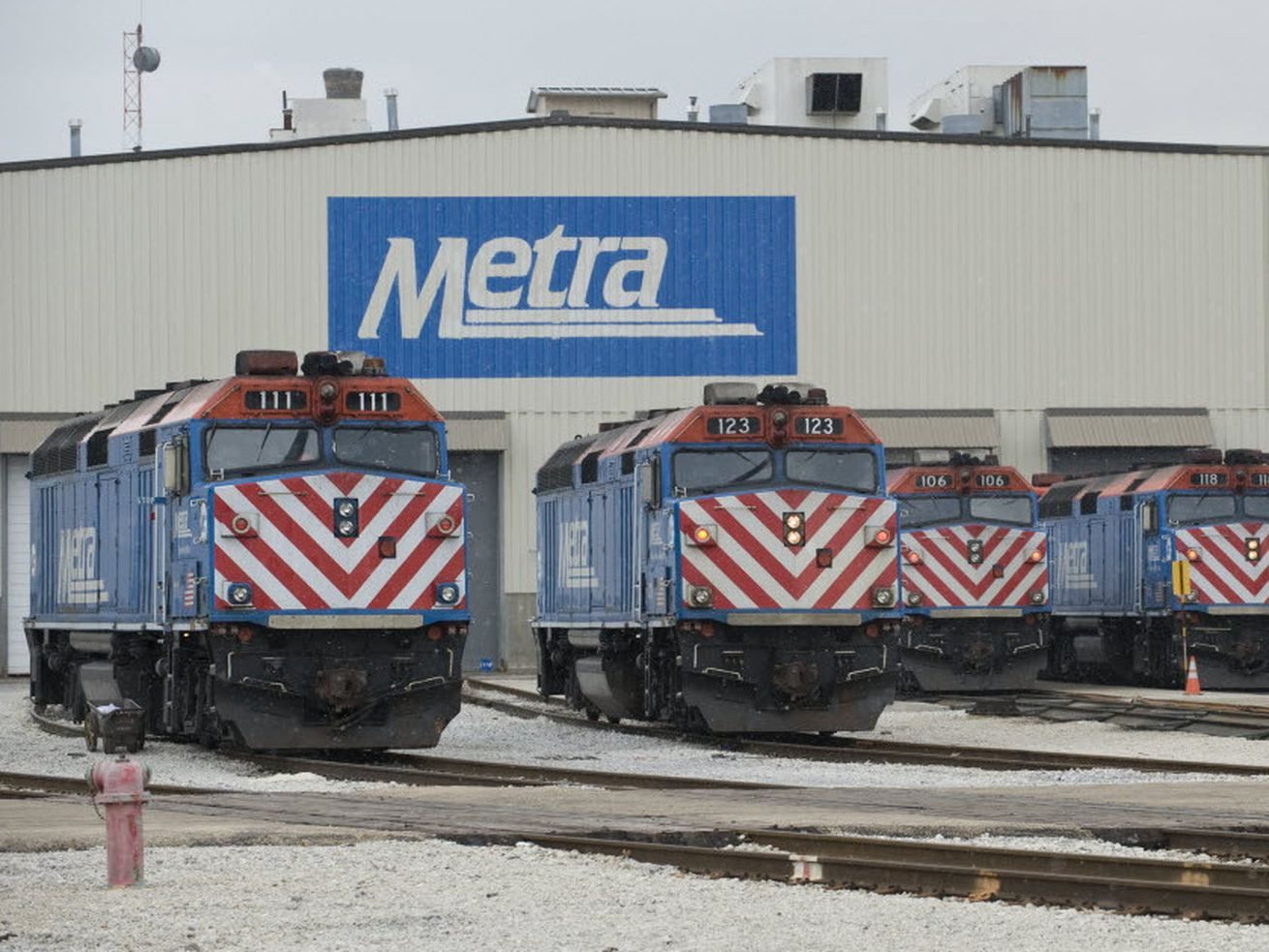 Metra trains outside a train barn.