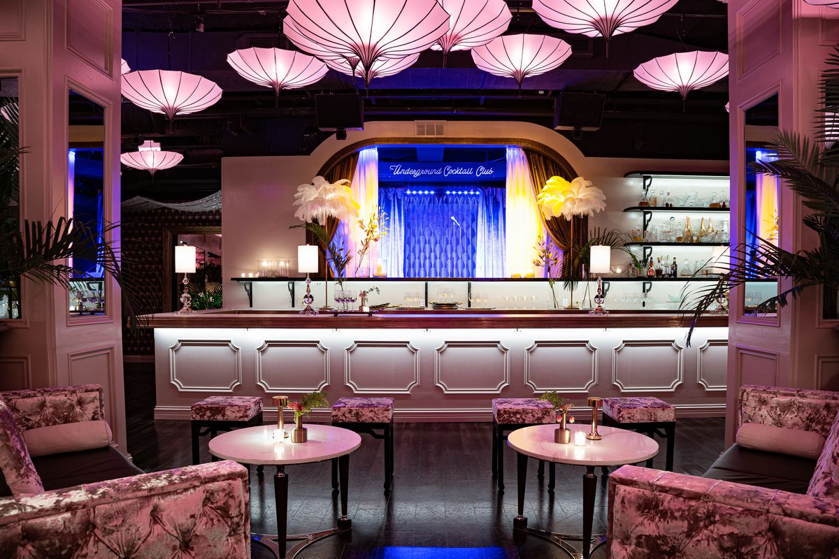 a bar with pink lighting, a blue backdrop, and two easy chairs with cocktail tables