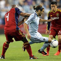 KANSAS CITY, KS - APRIL 14:  Graham Zusi #8 of Sporting Kansas City is tripped by Jamison Olave #4 of Real Salt Lake during the Major League Soccer game on April 14, 2012 at Livestrong Sporting Park in Kansas City, Kansas.  (Photo by Jamie Squire/Getty Images)