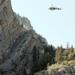A Department of Public Safety helicopter and crew along with members of the Utah County Search and Rescue work to secure and recover the body of an adult male from a very steep rock face west of Bridal Veil Falls in Provo Canyon on Sunday, July 18, 2021. The man fell on Saturday afternoon while climbing with a juvenile who did not witness the accident.
