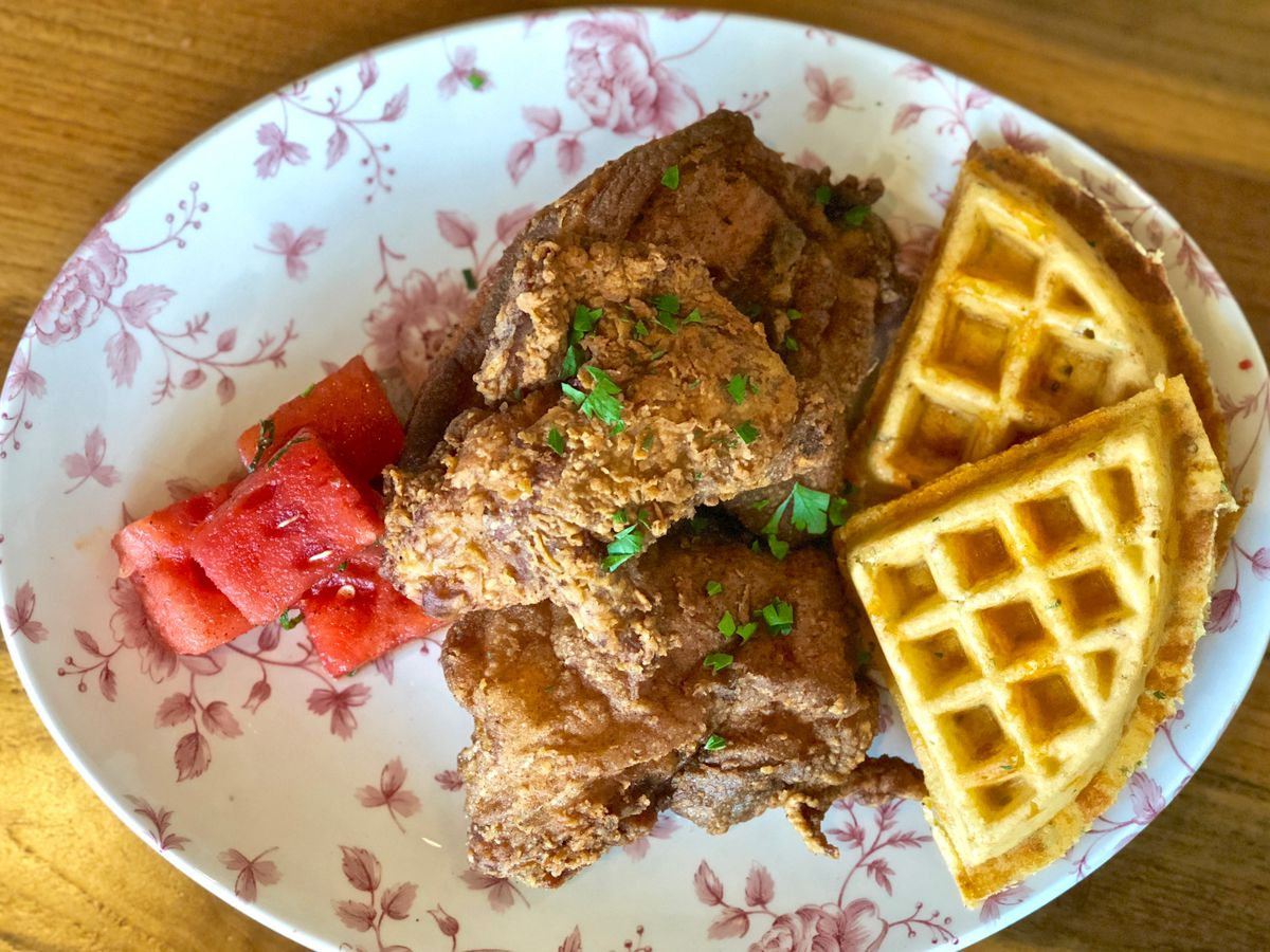 Fried chicken and waffles from Yardbird on a decorated plate.