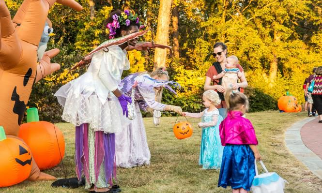 Kids in Halloween costumers receiving candy from a woman dressed as a which.