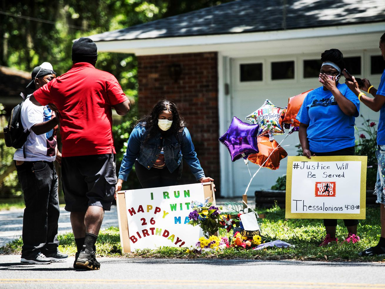 Gathered on the frontlawn, standingon the grasswithballoons and flowers, a group of black demonstrators hold signsatamemorial for Ahmaud Arbery near where he was shot and killed in Brunswick, Georgia, on May 8.