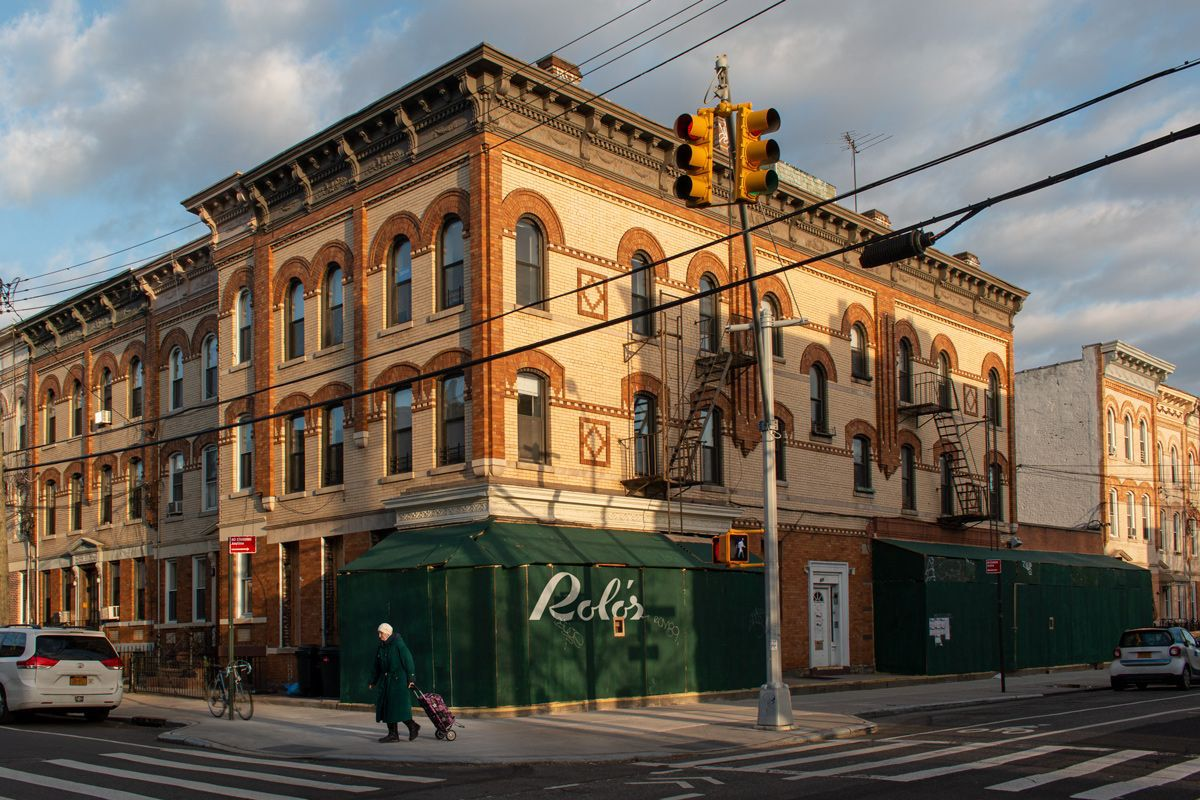 The exterior of a brick and stone building with green construction scaffolding that bears the words Rolo's