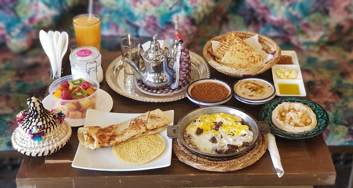 A small wooden table filled with dishes on various plates including flatbreads, a fruit bowl, dips, a tray of tea, and a glass of orange juice