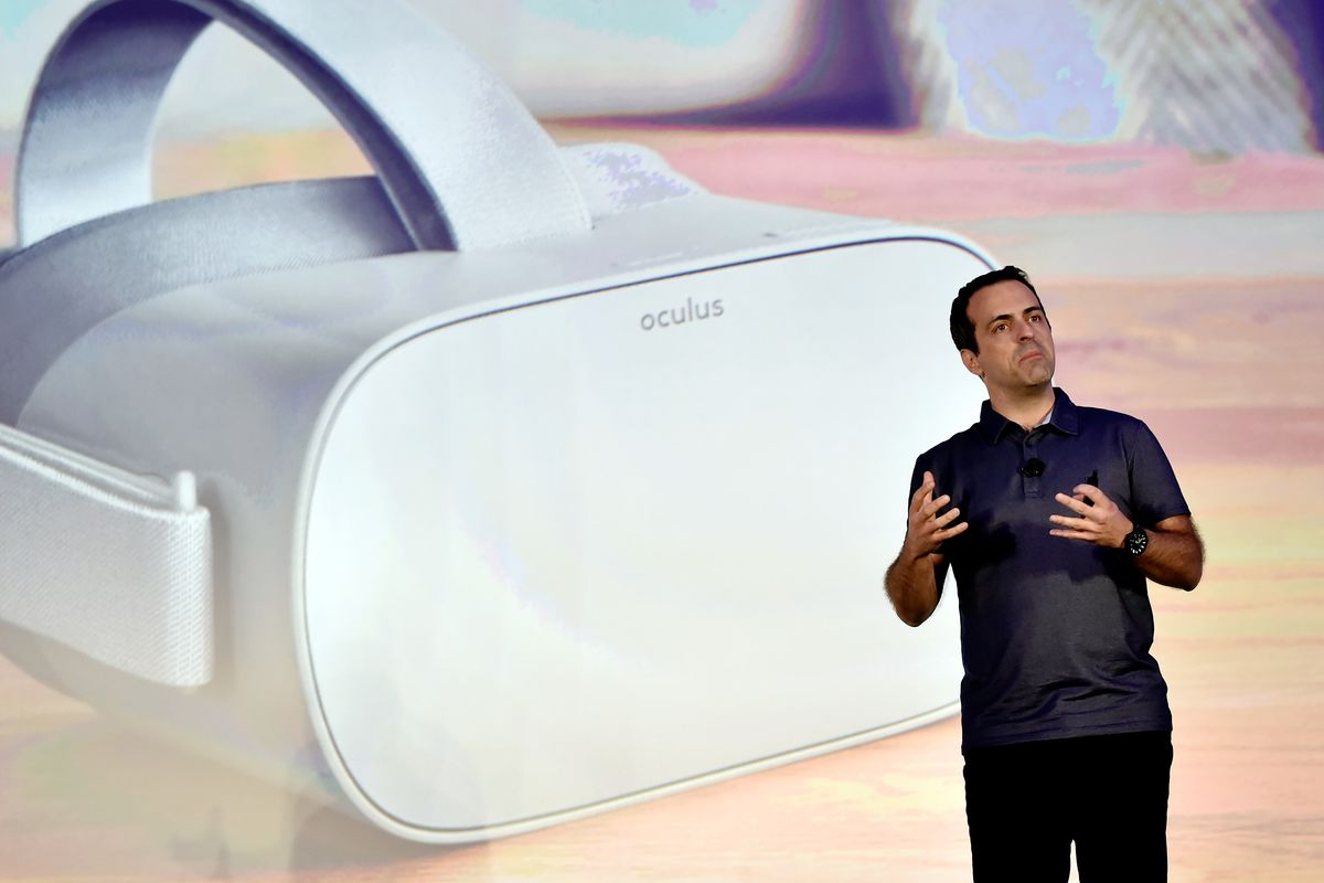 Facebook Vice President of VR Hugo Barra speaks onstage in front of a large picture of an Oculus VR headset.