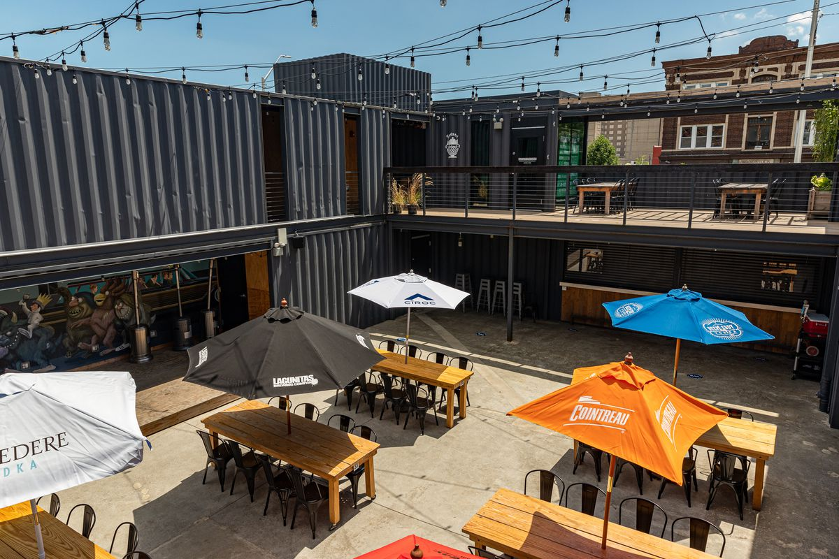 Detroit Shipping Company's outdoor courtyard tables are shown on a sunny day from a view on the second floor of the shipping container building. Tables are covered with white, black, blue, and orange umbrellas.