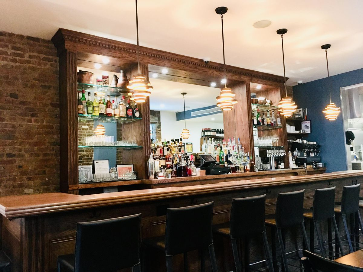 A long wooden bar with black stool seating