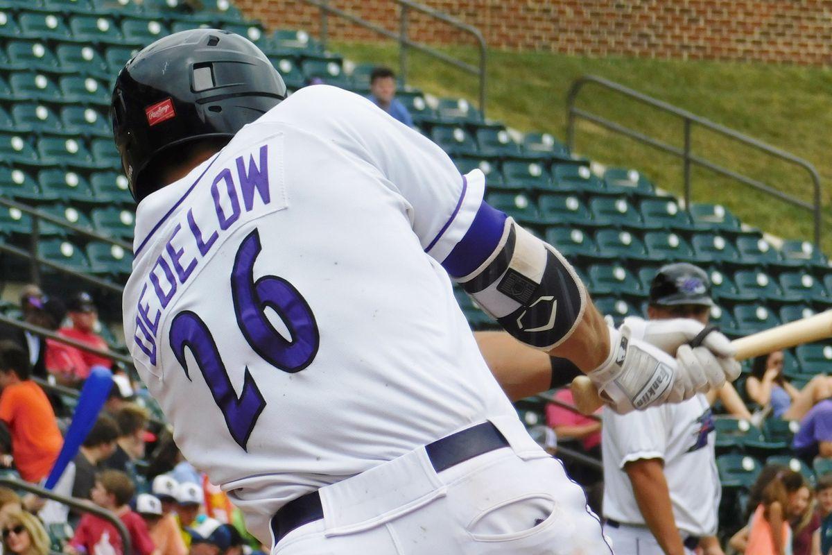 Craig Dedelow #26 bats from behind, mid-swing