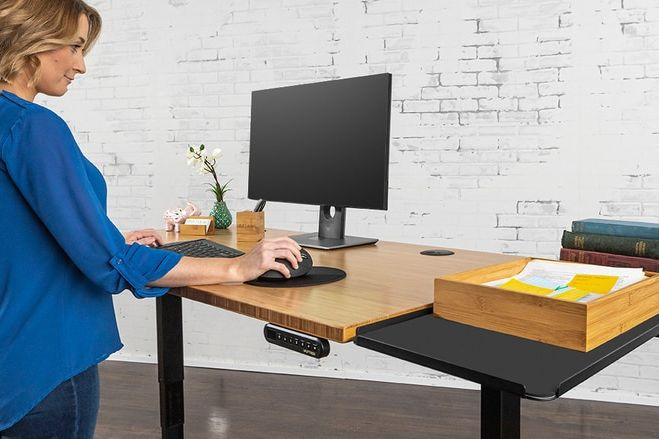 Woman stands next to a desk.