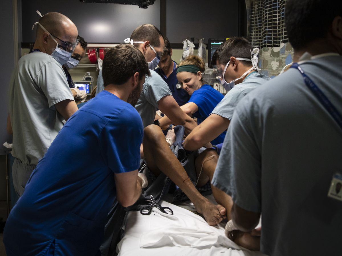 Medical workers perform their duties from specific positions around the bed as they treat a man with a stab wound at Mount Sinai Hospital.