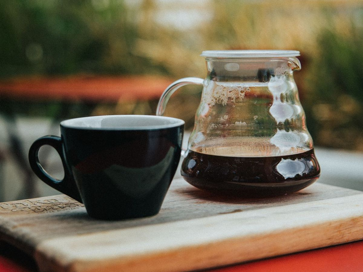 A black coffee cup and a pitcher with coffee in it.