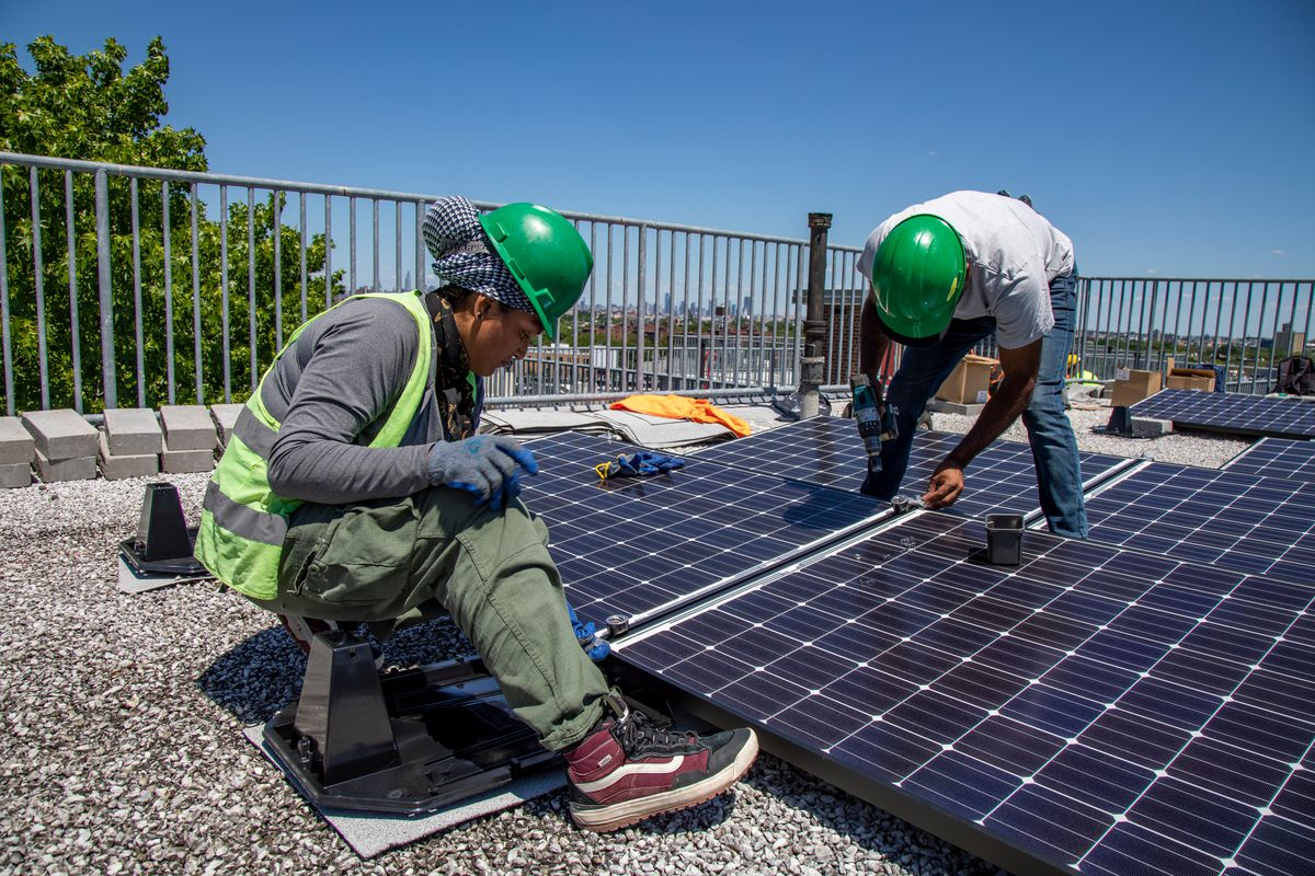 Workers install solar panels at NYCHA's Kingsborough Houses in Crown Heights.