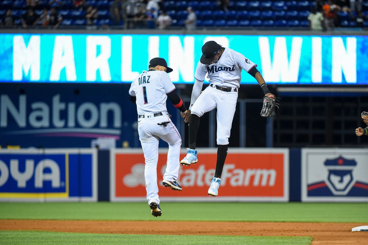 Lewis Brinson #25 of the Miami Marlins high fives Isan Diaz after defeating the New York Mets at loanDepot park