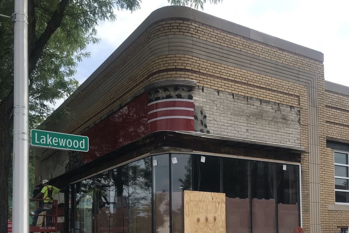 The curved facade of the Kresge building has light colored bricks, glass windows, and red tile. It is surrounded by construction material including plywood boards.