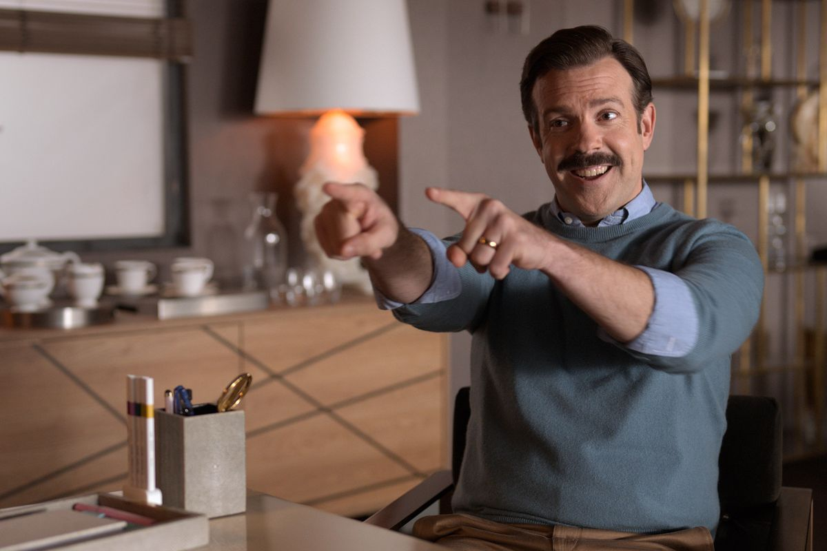 Ted Lasso (actor Jason Sudeikis), with neatly combed hair and a thick mustache, jovially points with both fingers across a desk in a fancy modernist office.