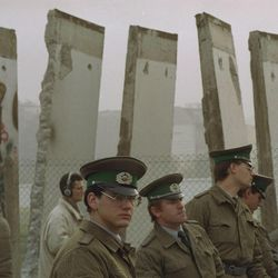 East German border guards are pictured Monday, November 13, 1989, in front of segments of the Berlin Wall, which were removed to open the wall at Potsdamer Platz passage, Sunday.