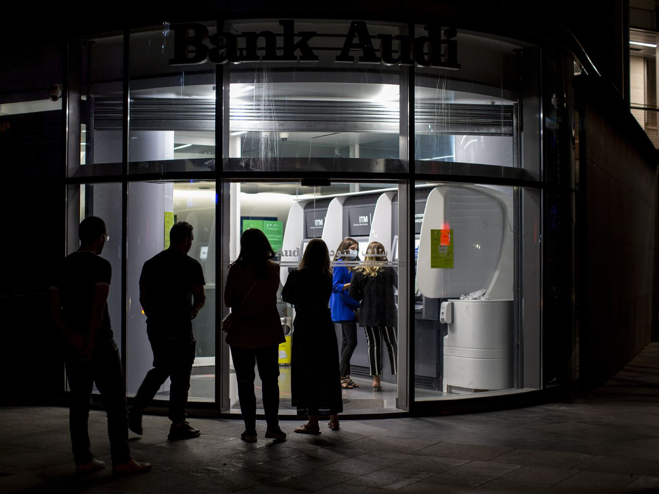 Clients wait to use ATM machines outside a closed bank in Beirut, Lebanon, Wednesday, June 2, 2021.
