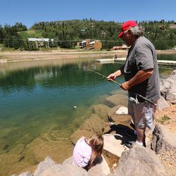 George Mayne fishes with his grandchildren as the Brian Head Fire continues to burn in southern Utah on Friday, June 30, 2017. The evacuation order for Brian Head and Dry Lakes was lifted Friday, 13 days after residents were forced from their homes by the raging fire.