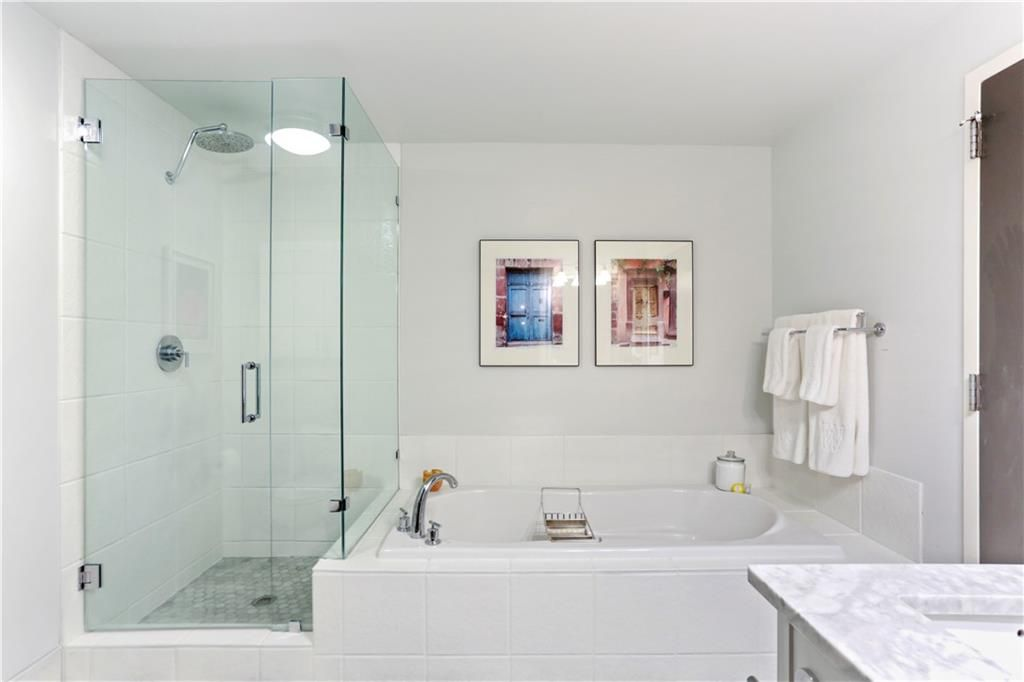 a white master bathroom with a large tub and bath.