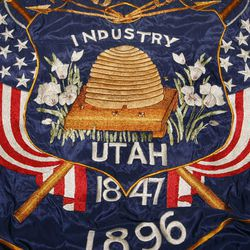 """Emma W. """"Dolly"""" McMonegal created this multicolored embroidered Utah flag in 1922. She forgot to put the year 1847 on the flag and had to add it later below the shield. All current Utah flags are based on this version of the flag -- even though state law requires 1847 to be on the shield, not below it."""