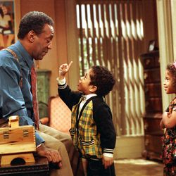 """Bill Cosby, as Dr. Cliff Huxtable of """"The Cosby Show,"""" listens to a point made by his grandson Gary Gray, as his granddaughter played by Jessica Vaughn looks on during taping of the final episode before a live studio audience in New York City, Friday, March 6, 1992."""