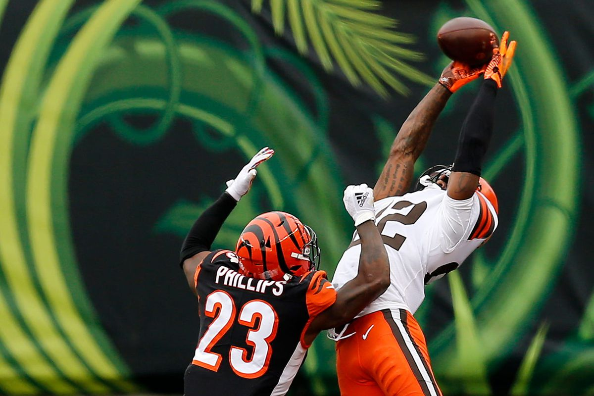 Cleveland Browns wide receiver Rashard Higgins (82) makes a leaping catch over Cincinnati Bengals cornerback Darius Phillips (23) in the fourth quarter of the NFL Week 7 game between the Cincinnati Bengals and the Cleveland Browns at Paul Brown Stadium in downtown Cincinnati on Sunday, Oct. 25, 2020. The Bengals and Browns exchanged late touchdowns, finishing in a 37-34 win for the Browns. Cleveland Browns At Cincinnati Bengals