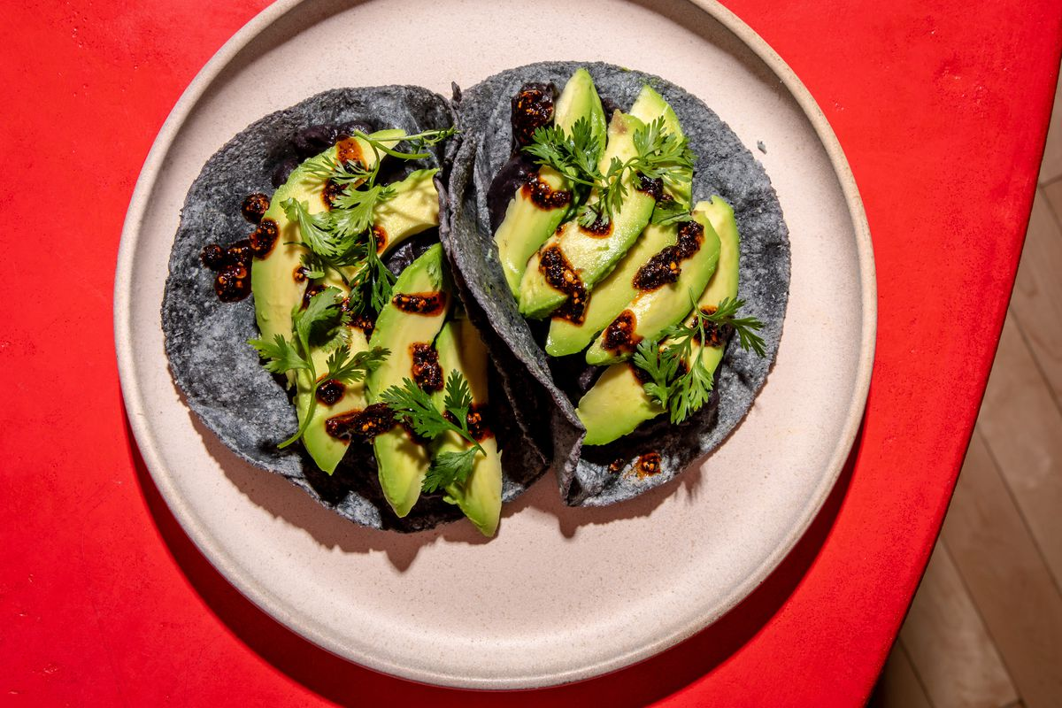 Slices of avocado sit above black beans on blue corn tortillas as part of a taco preparation