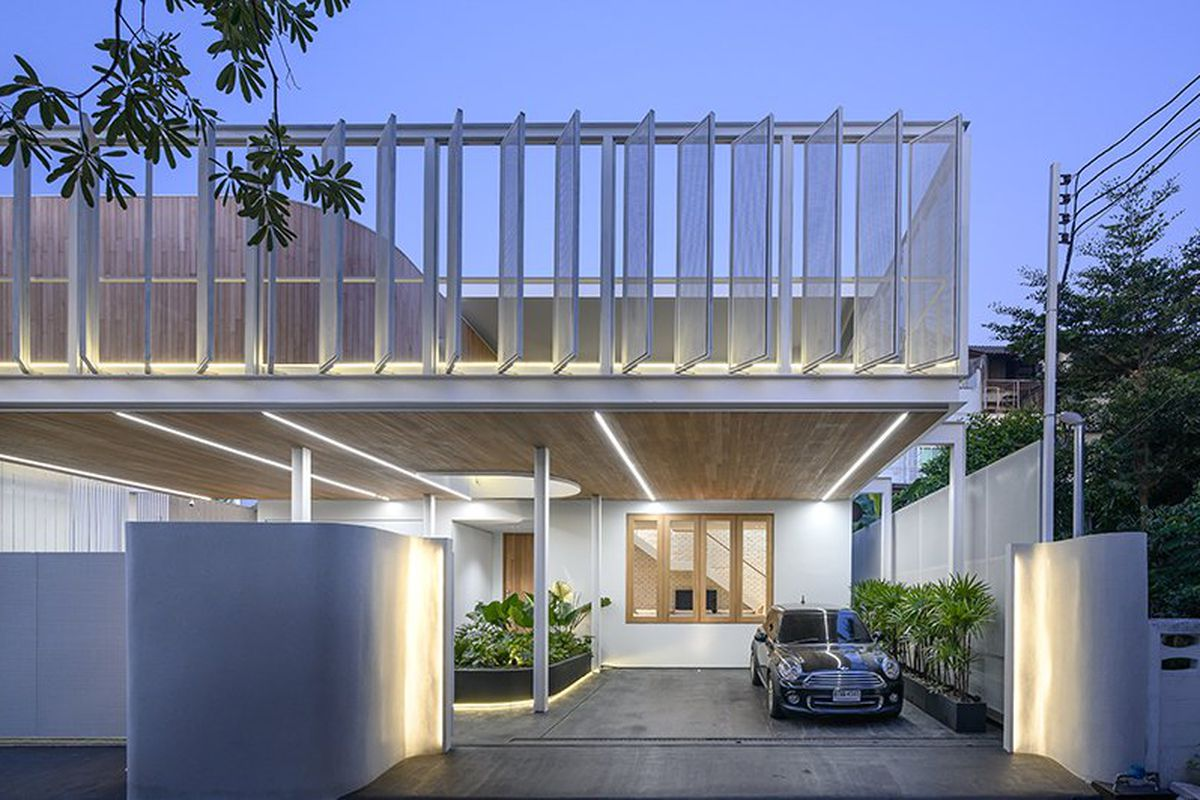 House illuminated at night has an open driveway and second-story terrace with white shutters.