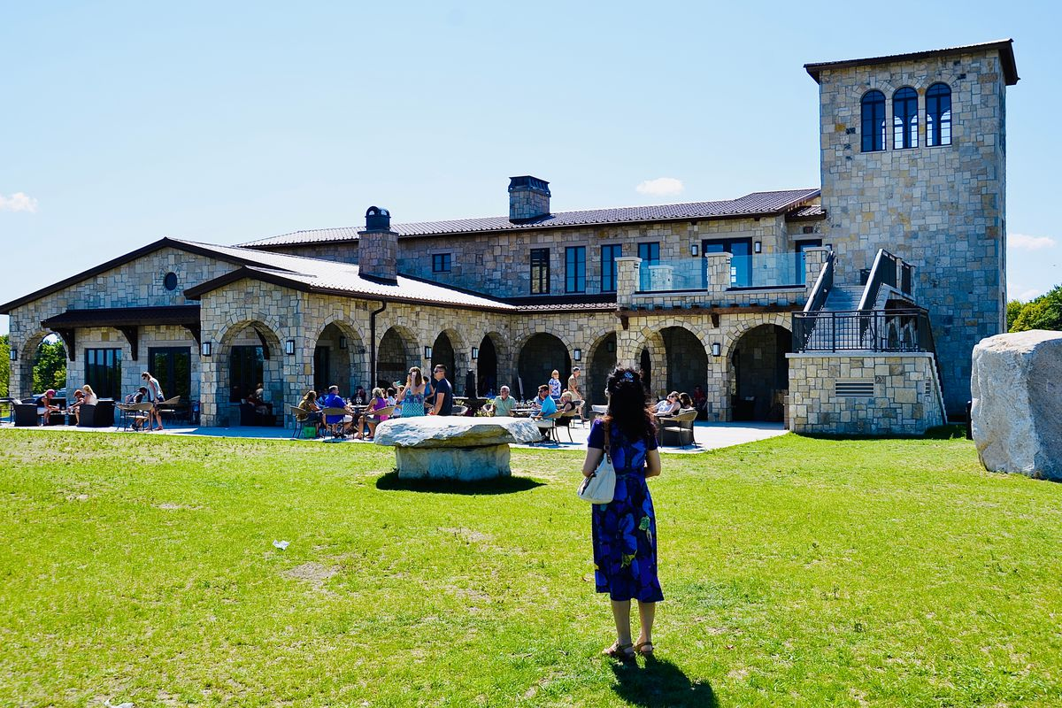 A woman in a blue dress stares across a grassy lawn in the direction of the stone building and patio at Mari Vineyards.