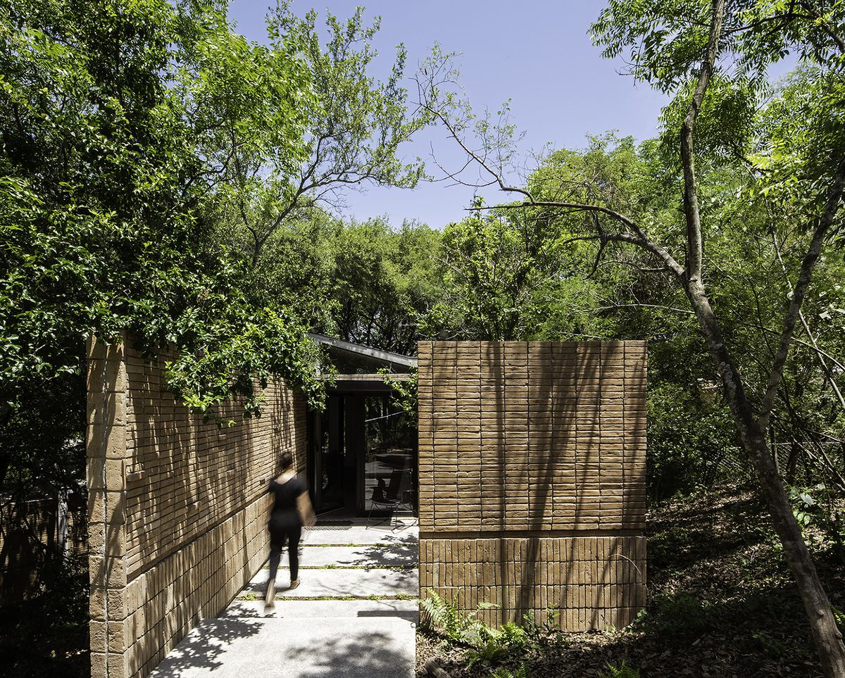 A woman walking into a brick house that has a wide entrance and trees surrounding it.