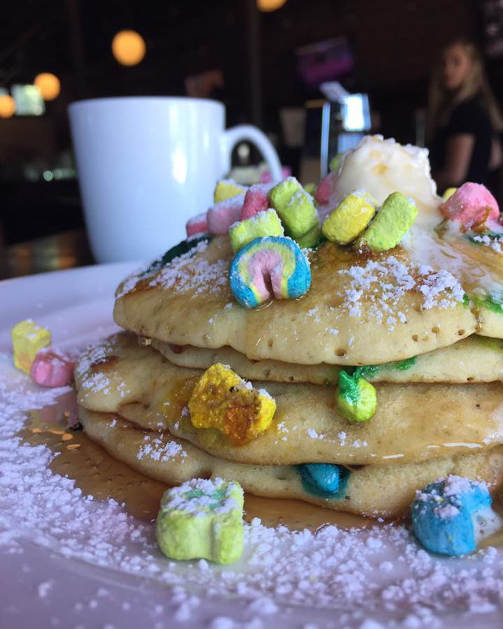 A stack of pancakes topped with pieces of Lucky Charms cereal, butter, and powdered sugar