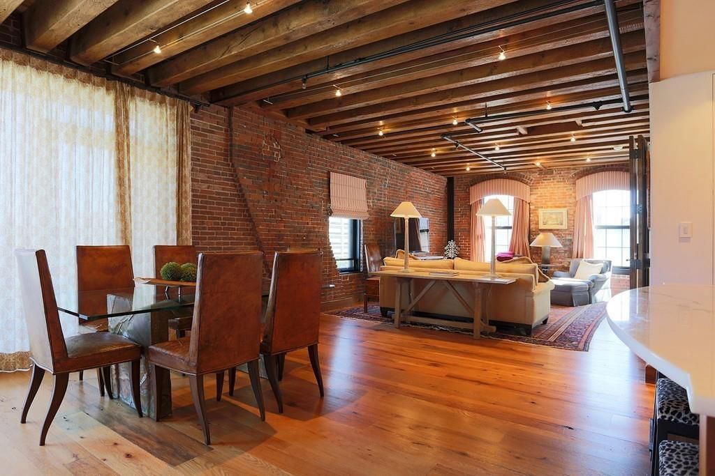 A sweeping dining room-living room area with furniture, and there are wood beams covering the ceiling and exposed brick along one wall.