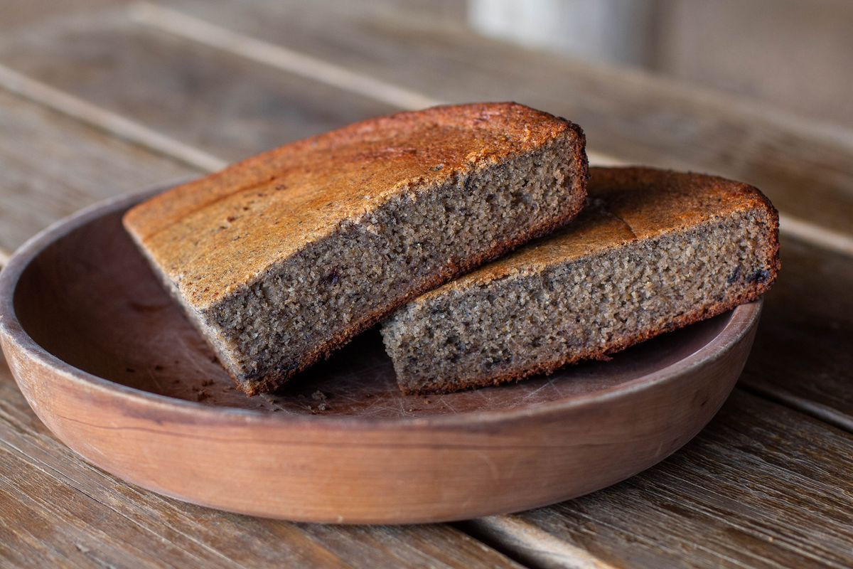 Two slices of light brown corn bread that has been cut in quarter-circle slices, on top of a wooden plate with raised edges, on a wooden table