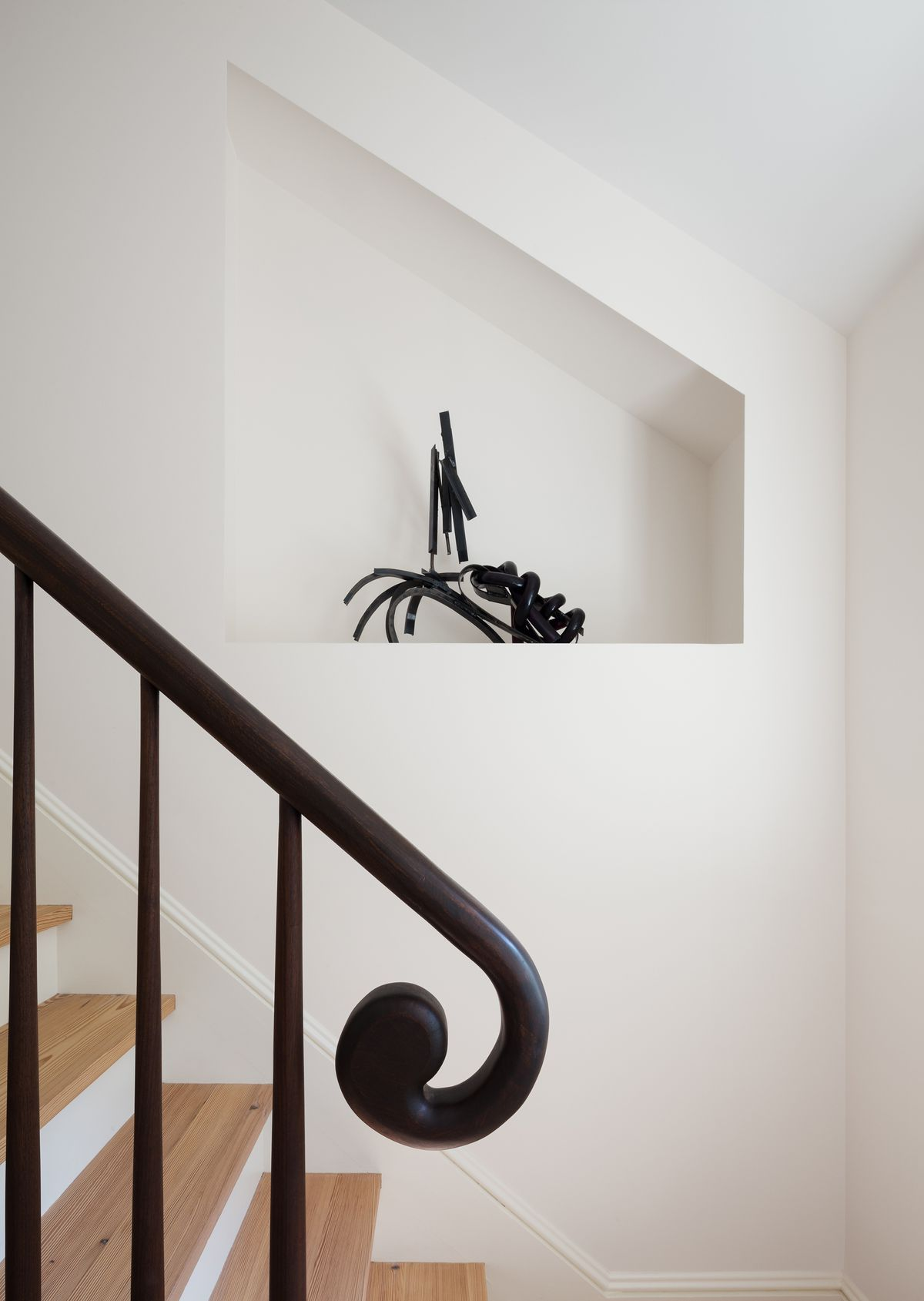 A black stair rail. The bottom of the stair rail is a curl shape. The stairs are hardwood and the walls are painted white.