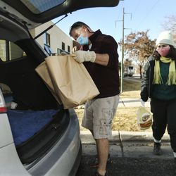 Matthew Palmer and Audrey Mancini place food items into a trunk at a Crossroads Urban Center food distribution event at Rowland Hallin Salt Lake City on Wednesday, Dec. 23, 2020. This year's Christmas food distribution marks the 23rd year of collaboration with Rowland Hall. Crossroads has been providing social services to individuals and families in need in Salt Lake City and the surrounding areas for over 50 years. Funding and support for the Christmas food distribution came from the staff, students and families of Rowland Hall, the Utah Food Bank, the Eccles Broadcast Center at the University of Utah, the B.W. Bastian Foundation, Rocky Mountain Power, and dozens of other individuals and local religious congregations.