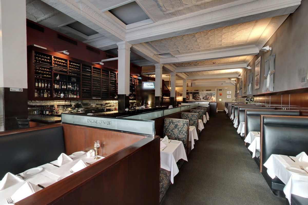 The inside of a long finer dining restaurant with white tablecloths, lots of booths, and a wooden bar to one side.